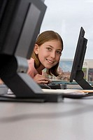 Girl 9-11 using computer at desk in classroom, smiling, side view, portrait differential focus