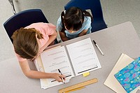 Two girls 9-11 studying at desk in classroom, overhead view
