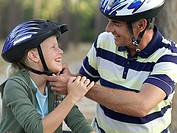 Father adjusting strap of daughter´s 9-11 cycling helmet, smiling, side view