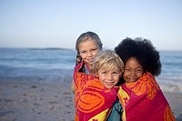 Three children 6-9 standing on beach, wrapped in towel, smiling, front view, portrait