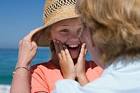 Senior woman placing straw sun hat on granddaughter's head, girl 8-10 smiling differential focus