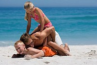 Father playfighting with two children 8-10 on sandy beach, smiling