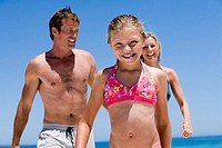 Two generation family in swimwear walking on beach, smiling, front view