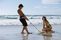 Teenage couple 13-15 playing on beach, boy pulling girl along sand on bodyboard, profile