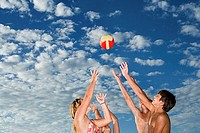 Group of teenagers 13-15 playing with ball on beach, hands raised, smiling, side view