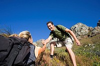 Couple ascending mountain, man offering woman helping hand, smiling, low angle view