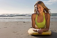 Teenage girl 17-19 lying on top of bodyboard on sandy beach, smiling, front view, portrait