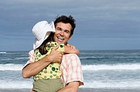Father embracing daughter 6-8 on beach, smiling, sea in background