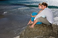 Teenage couple 17-19 sitting on rock at beach near water's edge, smiling, profile