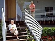 Senior couple relaxing at home, man standing on veranda, woman sitting on steps, smiling, portrait