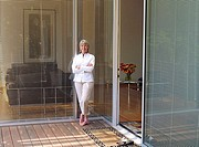 Senior woman standing on patio beside sliding doors, smiling, arms folded, portrait