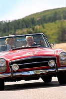 Senior couple driving along country road in red convertible car, smiling, front view