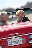 Senior couple driving along country road in red convertible car, smiling, rear view, portrait
