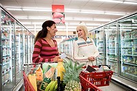 Two women shopping in supermarket, standing beside trolleys in aisle, talking, smiling