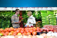 Couple shopping in vegetable section of supermarket, smiling, side view