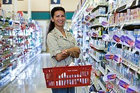Woman shopping in supermarket, carrying basket, smiling, side view, portrait