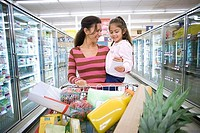 Mother and daughter 4-6 shopping in supermarket, woman pushing trolley in aisle, smiling