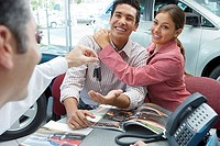 Young couple sitting at desk in car showroom, salesman handing key to man, smiling