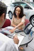 Salesman and young woman sitting at desk in car showroom, customer pointing at brochure, smiling