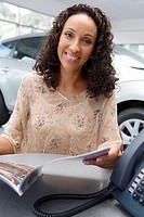 Young woman sitting at desk in car showroom, looking at brochure, smiling, portrait