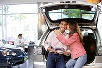 Salesman in car showroom, focus on woman kissing man on cheek beside new hatchback in foreground