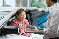 Couple in car showroom, man holding brochure, woman sitting in driver's seat of new car, smiling