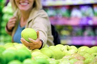 Woman choosing green apple from display in supermarket, smiling differential focus
