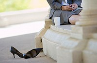 Businesswoman sitting alone on coffee break, shoes off and feet up, outdoors, low section tilt