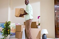 Man moving house, stacking cardboard boxes in living room, smiling, side view, portrait