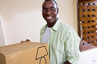 Man moving house, holding cardboard box in living room, smiling, portrait