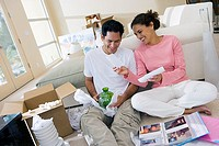 Couple moving house, sitting on floor in room, man unpacking glassware, woman looking at photographs tilt