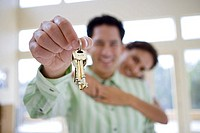 Couple standing in room, man holding aloft keys to new house, smiling, portrait differential focus