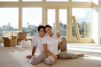 Couple moving house, sitting on bare living room floor, man with arm around woman, smiling, portrait