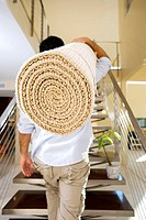 Man moving house, carrying rolled-up carpet on shoulder up staircase, rear view