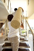 Couple moving house, carrying rolled-up carpet on shoulders up staircase, rear view