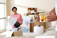 Couple moving house, woman unpacking lamp in living room, focus on man carrying two mugs