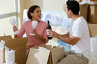 Couple moving house, woman holding two wine glasses in living room, man holding bottle of wine, smiling