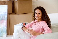 Woman moving house, sitting on floor in living room, holding glass of wine, smiling, side view, portrait