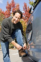 Man leaning against car bumper, tying shoelace, smiling, portrait