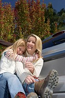 Girl 7-9 embracing mother beside car, woman sitting on bumper, tying shoelace, smiling, portrait