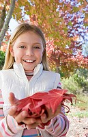Girl 7-9 holding autumn leaves in park, smiling, close-up, portrait