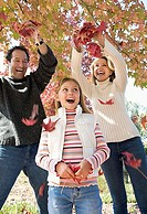 Family playing with autumn leaves in park, parents pulling on branch, daughter 7-9 laughing