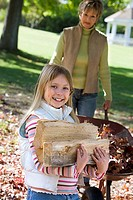 Woman pushing wheelbarrow in autumn garden, focus on daughter 7-9 carrying firewood, smiling, portrait