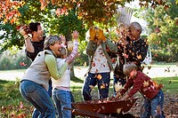 Multi-generational family playing with autumn leaves in garden, laughing, side view