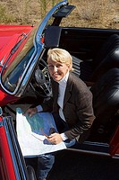 Mature woman sitting in red convertible car, looking at road map, smiling, portrait, elevated view