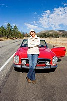 Mature woman standing in front of red convertible car on country road, smiling, front view, portrait