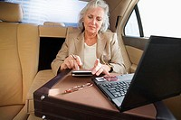 Senior businesswoman, with briefcase, sitting in back-seat of car, using personal electronic organiser and laptop