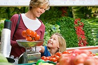 Mother and daughter 7-9 shopping in supermarket, woman weighing bunch of tomatoes in vegetable section, smiling