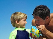 Father inflating water wing for son 4-6 at beach, boy looking on, smiling, close-up