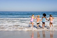 Four children 6-10 playing in Atlantic surf at beach, side by side, rear view